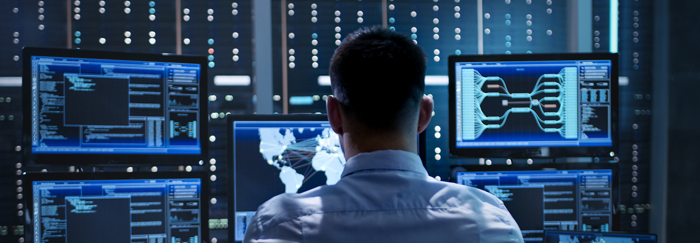 Federal cybersecurity worker sitting behind many monitors