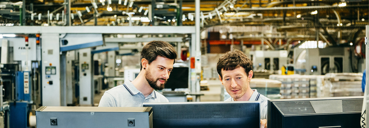 Men reviewing a supply chain at a technology plant