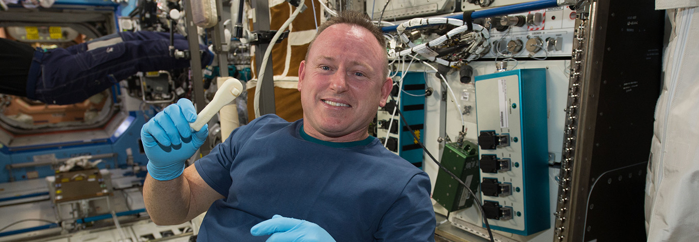 "International Space Station Expedition 42 Commander Barry ""Butch"" Wilmore shows off a ratchet wrench made with a 3D printer on the station."