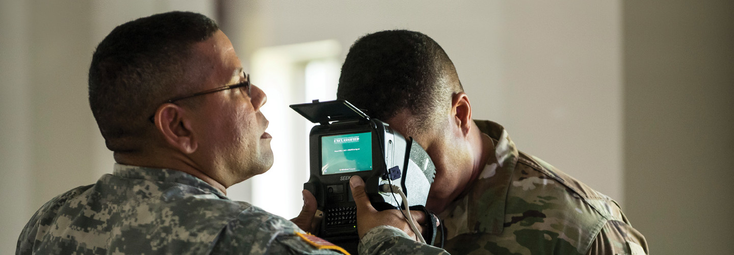 U.S. Army Reservists learn how to use iris scans to identify personnel during a training exercise.