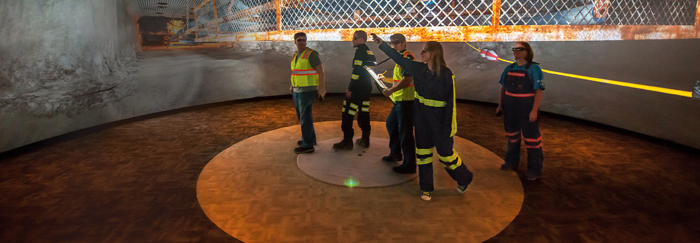 Research Lead Jennica Bellanca guides NIOSH workers through a virtual scenario on how to safely escape from a mine emergency. Each worker has a controller to operate the VR; the captain's navigates them through the exercise. At left, what the 360-degree space looks like without VR.