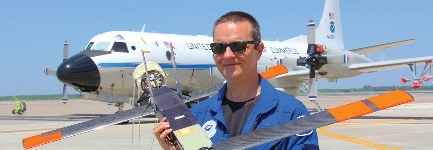 Joe Cione holding a drone and standing in front of a plane