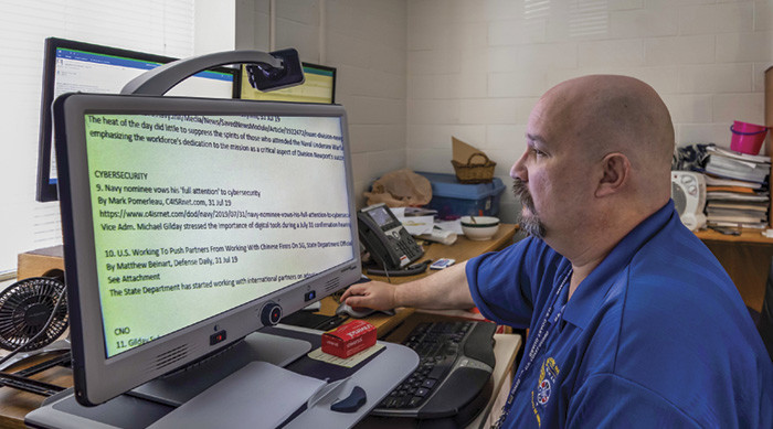 John Tebo, who works at the  Naval Undersea Warfare Center, uses a special device to help him read text and do his job.