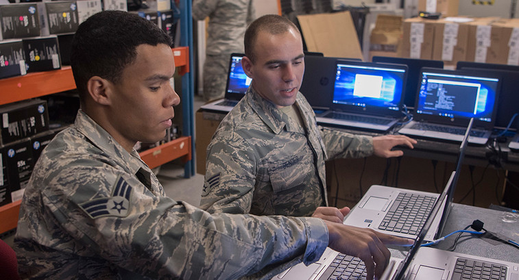 Senior Airmen Jonathon Clayton, left, and Dylan Bender, 21st Communication Squadron client systems technicians, work together to bring new Windows 10 laptops into compliance with Air Force standards at Peterson Air Force Base, Colo., March 22, 2017.