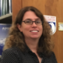 woman with curly long hair and glasses