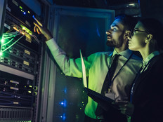 Man and woman checking cybersecurity sensor in a data center