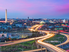Washington DC skyline at dusk with traffic moving on highways in streams of lights